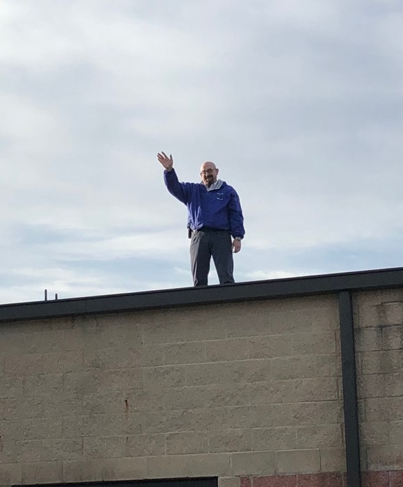 Mr. Abel greeting students from the roof of the school.